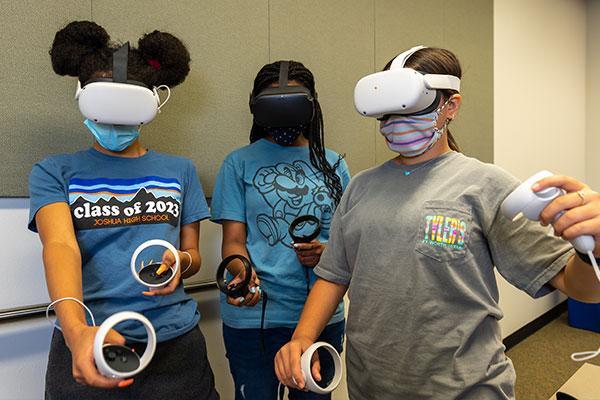 Three female grade school students holding VR goggles.